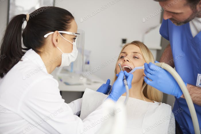 Two dentists doing their work in dentist's clinic
