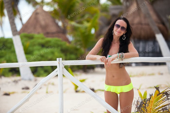 Young sexy woman in swimsuit near white fence at exotic resort