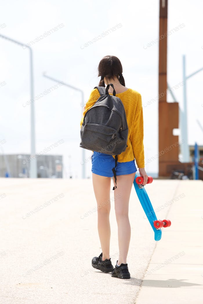 Young woman walking away with bag and skateboard