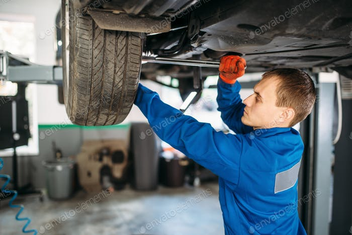 Mechanic repairs the suspension, car on the lift