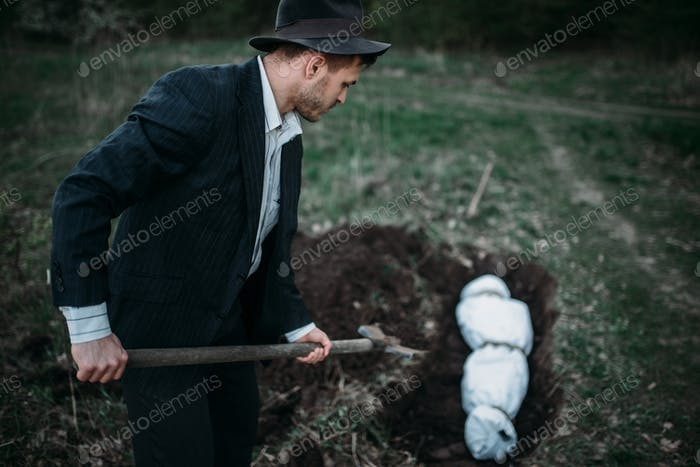 Maniac with shovel buries victim into a grave