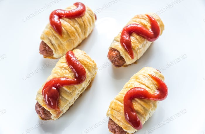 Sausage rolls under tomato sauce isolated