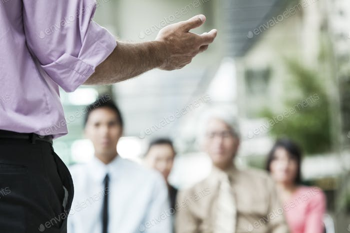 A closeup of a hand gesturing to a group of business people in a meeting.