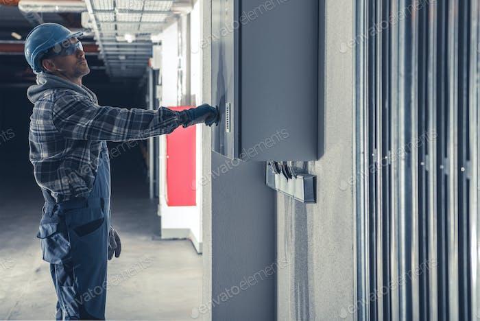 Técnico de instalación eléctrica delante de la caja de fusibles principal
