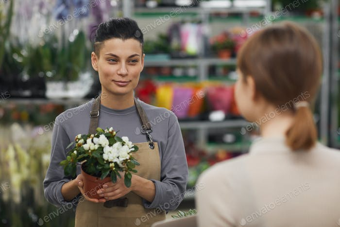 Mujer joven moderna venta de flores en la tienda