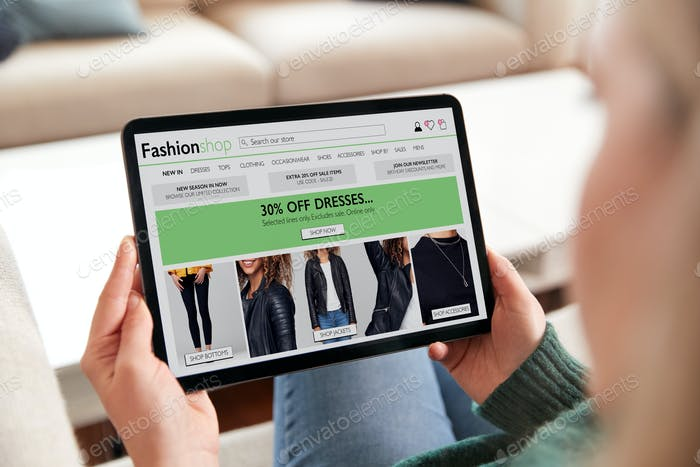 Close Up Of Woman Shopping For Clothes Online At Home Using Digital Tablet App