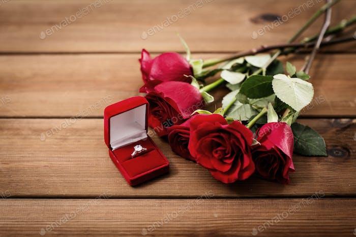 Nahaufnahme von Diamant Verlobungsring und roten Rosen