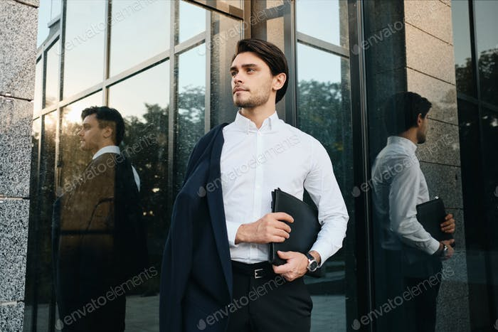 Young handsome man in jacket looking aside with bag for documents standing near glass building