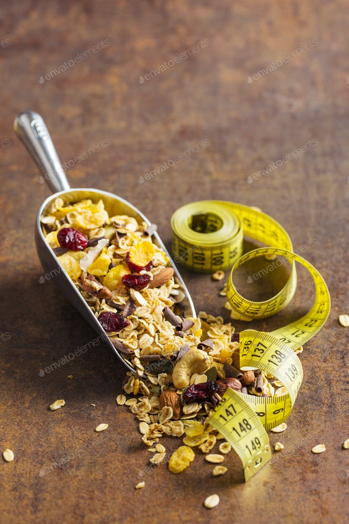 Tasty homemade muesli with nuts and measuring tape.
