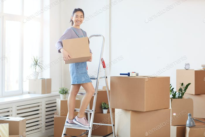 Smiling Asian Woman Unpacking Boxes in New House
