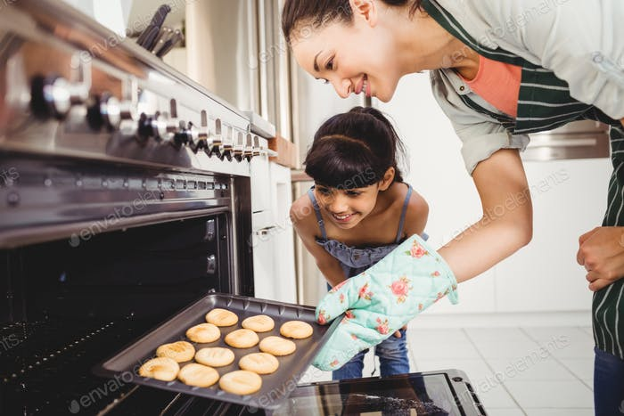 Happy mother and daughter placing cookies in oven at home