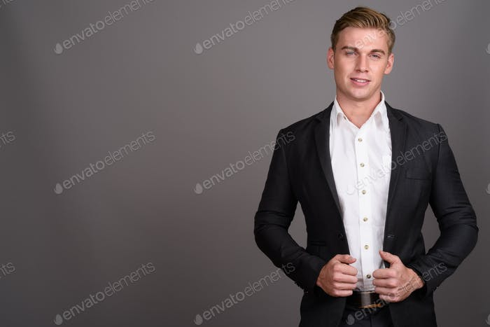 Young handsome businessman with blond hair wearing suit against