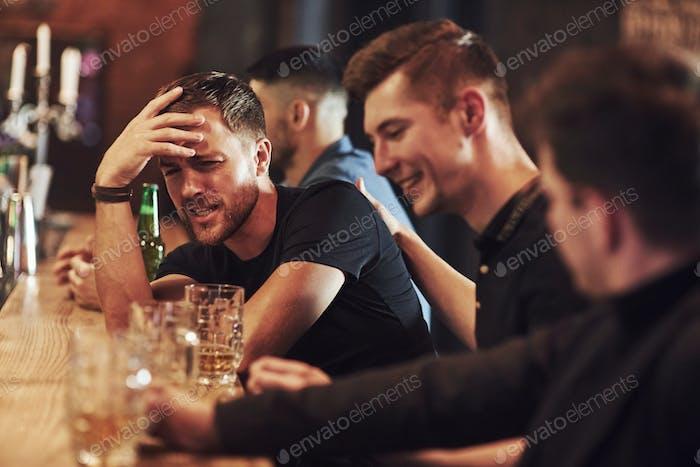 Seitenansicht. Freunde ruhen in der Kneipe mit Bier in den Händen. Konversation haben