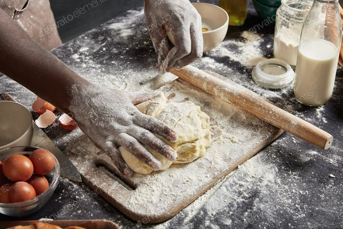 Cropped image of talented male cook shows how to bake delicious rolls, prepares dough, kneads it pro