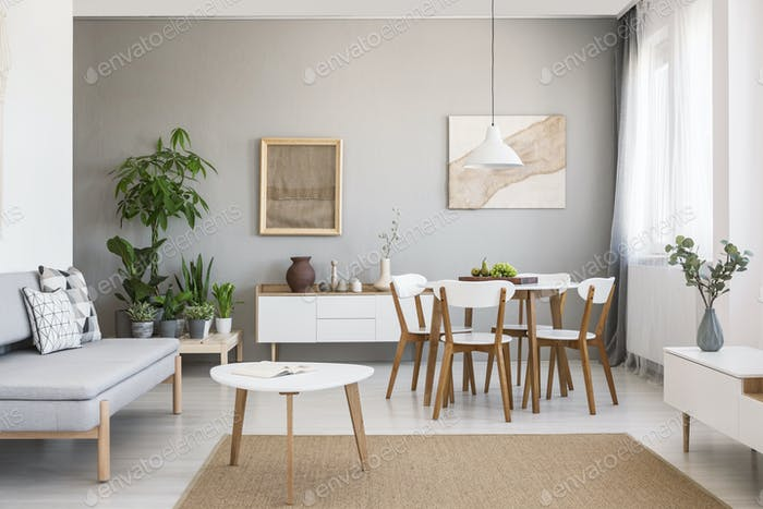 Real photo of a spacious dining and living room interior with wo