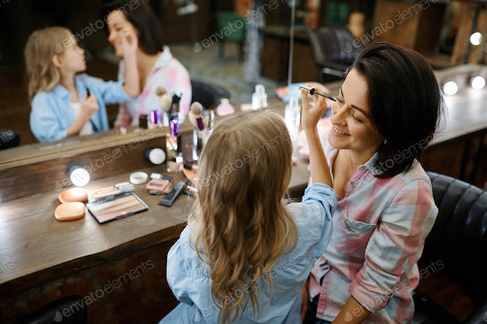 Daughter applies mascara for eyelashes to mother