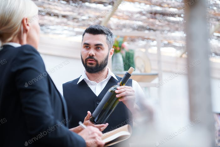 Young confident cavist with bottle of wine talking to his colleague