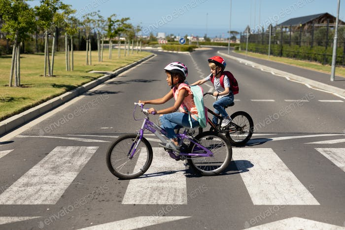 Schoolgirls crossing the road with bicycles