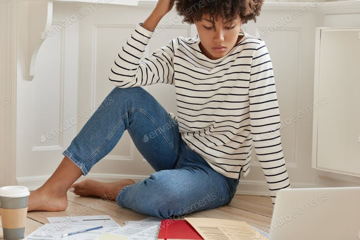 Photo of dark skinned woman checks paper graphics during remote job, plans budget income, checks bil