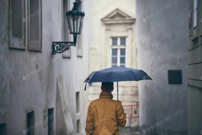 Lonely man with umbrella in rain