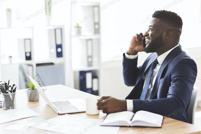 Black businessman talking on mobile phone, drinking coffee at office