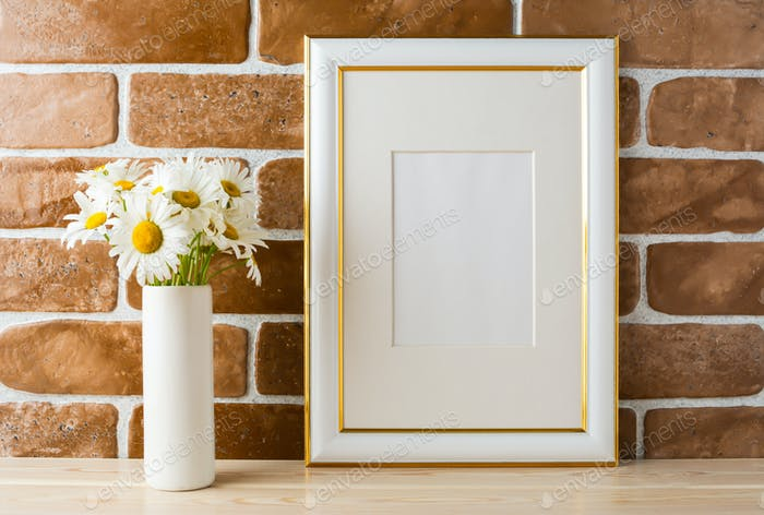 Gold decorated frame mockup with daisy bouquet exposed brick wal