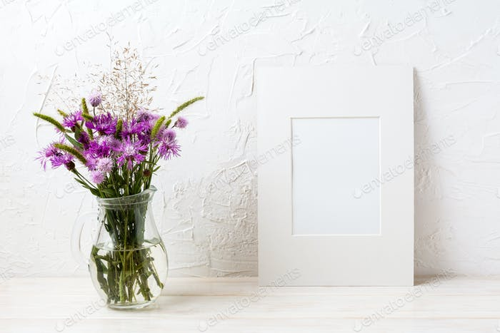 White frame mockup with purple burdock in the glass jug