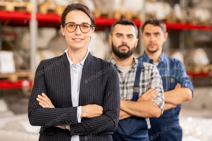 Young confident leader of team standing in front of two factory workers