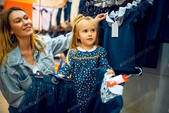 Mother and little baby choosing dress, kid's store