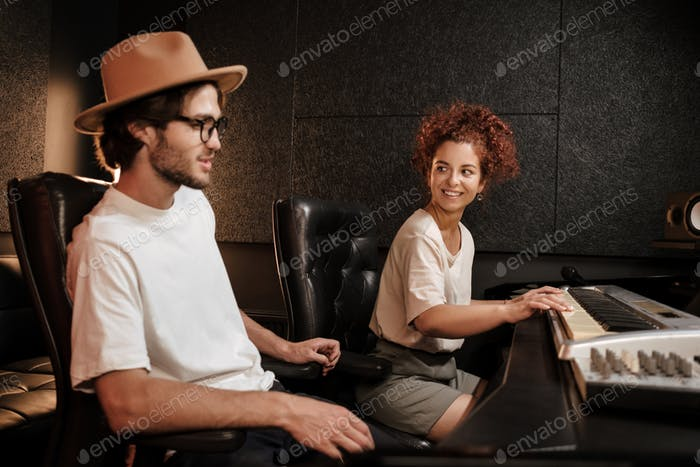 Young music band composing song on piano keyboard in modern sound recording studio