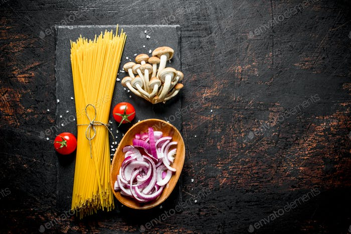 Raw spaghetti with tomatoes, mushrooms and cutting onion in bowl.