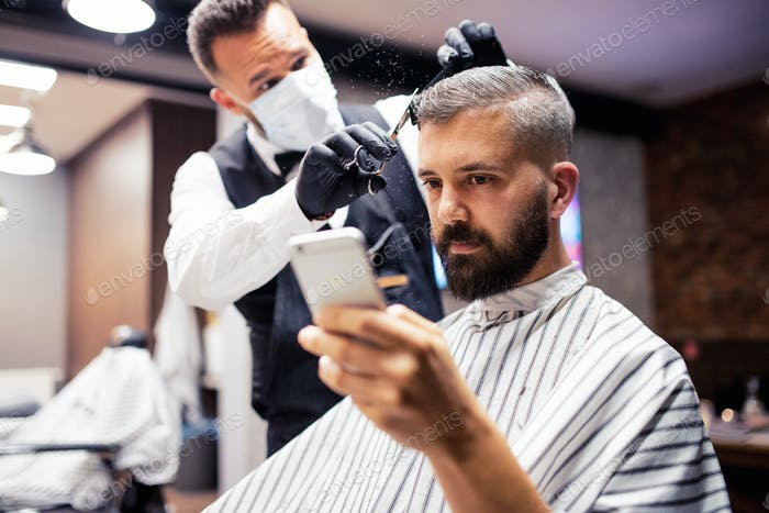 Hipster man client visiting haidresser and hairstylist in barber shop, taking selfie.