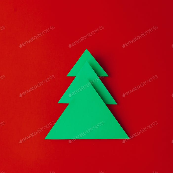 Minimal paper art Christmas tree on red background. Flat lay. New Year concept.