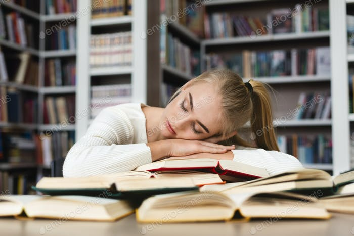 Young blonde girl having nap while studying at library