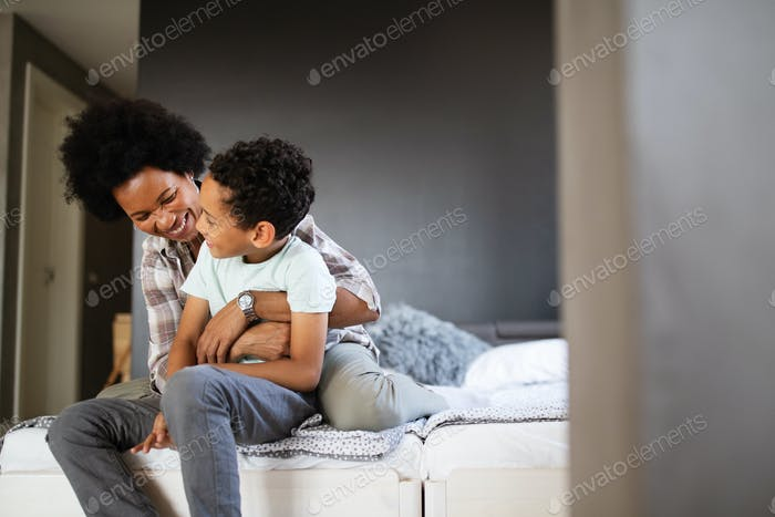 Happy mother playing, having fun, hugging with her son at home