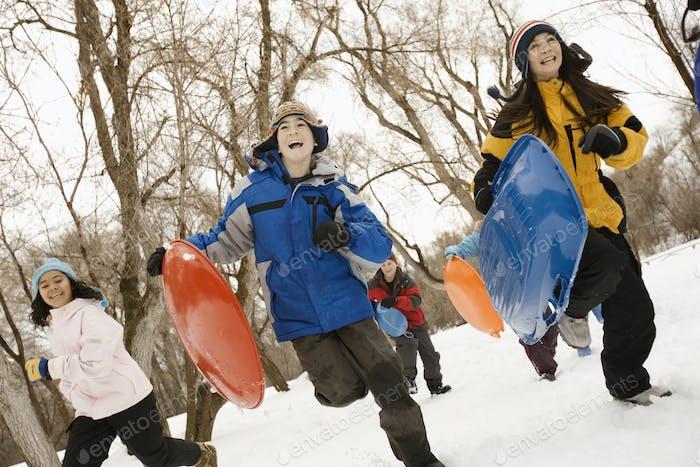 Eine Gruppe von Kindern, Jungen und Mädchen, die über den Schnee mit Schlitten laufen.