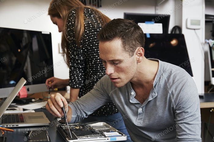 A young man and a young woman working on circuitry in a technology lab.