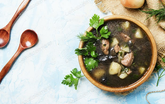 Homemade soup with meat and forest mushrooms
