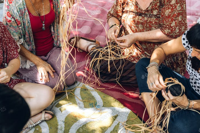 Different ages females weaving bascets on the craft workshop, sitting on a carpet on a flour