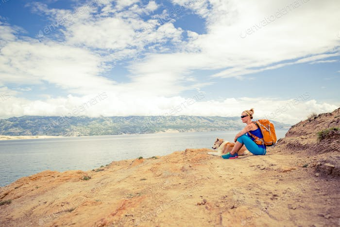 Woman hiking walking with dog on seaside trail