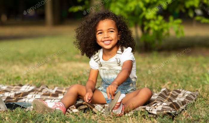 Adorable girl sitting on blanket at nature, enjoying summertime