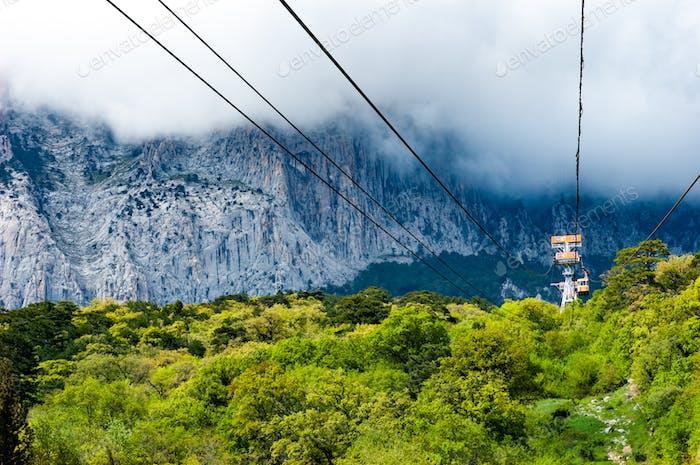 Standseilbahnen passieren durch malerische Dickicht Hintergrund Berge