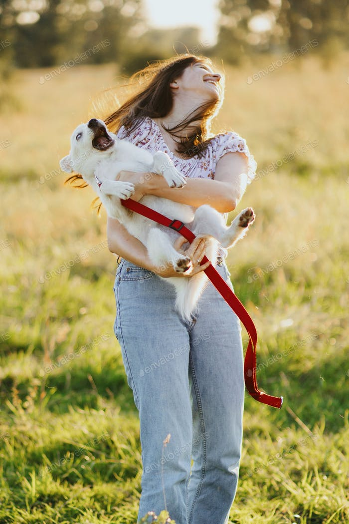 Girl holding playful adorable fluffy puppy