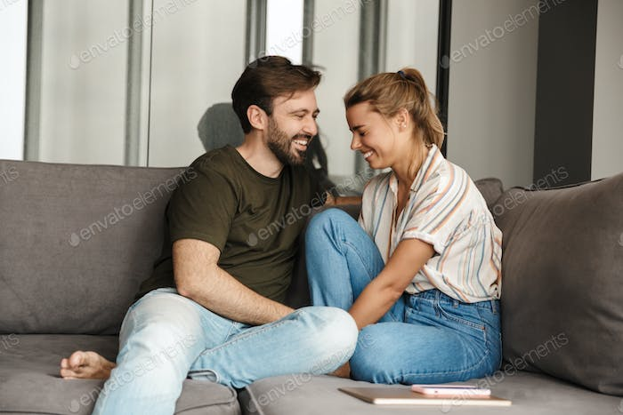 Photo of cheerful couple laughing and talking while sitting on sofa
