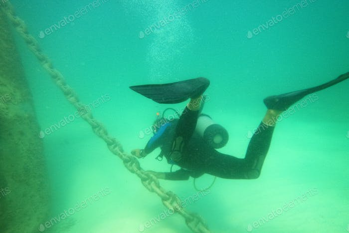 Male scuba diver with equipment diver swims in water