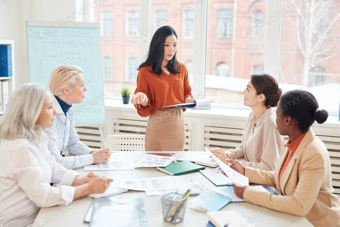 Asian Woman Giving Presentation at Business Meeting