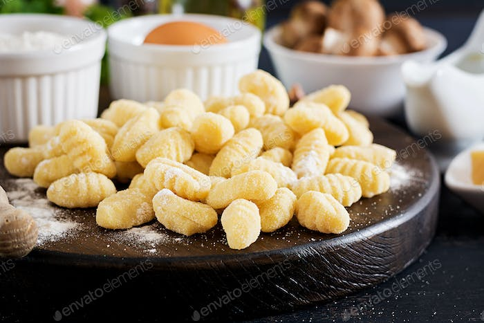 Uncooked homemade Gnocchi with a mushroom cream sauce and parsley  in bowl on a dark background.
