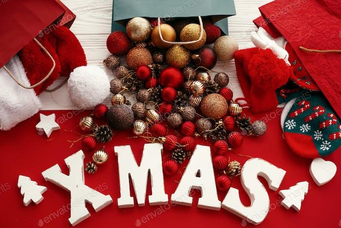 Weihnachtswort mit roten und goldenen Kugeln aus Tasche, Weihnachtsmütze und Strümpfen in Einkaufstaschen