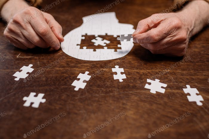 cropped view of ill senior man collecting jigsaw puzzle for dementia therapy