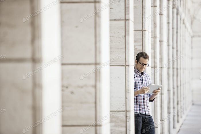 A man relaxing and checking his phone, sitting outside a building.